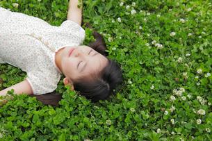 緑のクローバーの上で寝転がる女の子の写真素材 [FYI02027740]