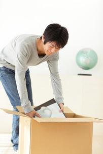 引っ越しの荷造りをする若い男性の写真素材 [FYI02027768]