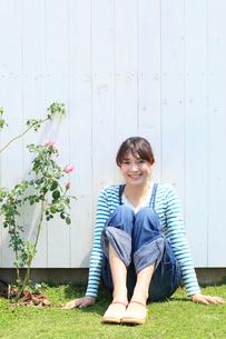 バラの咲く庭に座る女性の写真素材 [FYI02027771]