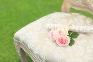 椅子の上の楽譜と小さなバラの花束の写真素材 [FYI02027792]