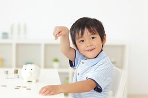 お金を持つ男の子と貯金箱の写真素材 [FYI02027809]