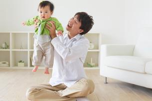 リビングでくつろぐ赤ちゃんとお父さんの写真素材 [FYI02027869]