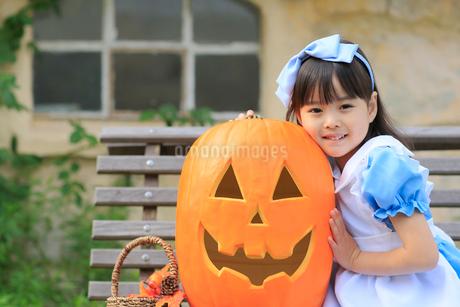 大きなカボチャとハロウィンの仮装をした女の子の写真素材 [FYI02027975]