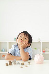 貯金箱の前で悩む男の子の写真素材 [FYI02028006]
