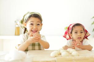 ピザ生地を丸める小さな女の子たちの写真素材 [FYI02028020]