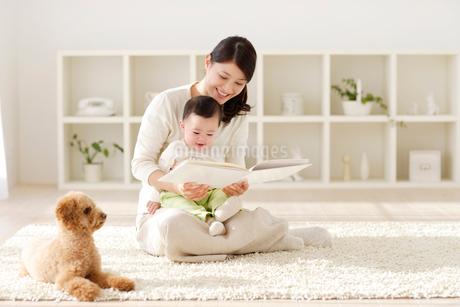 リビングでお母さんに抱っこされて絵本を読む赤ちゃんの写真素材 [FYI02028110]
