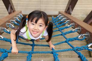 公園の遊具で遊ぶ元気な女の子の写真素材 [FYI02028141]