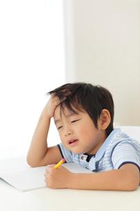 勉強中に頭を抱える男の子の写真素材 [FYI02028163]