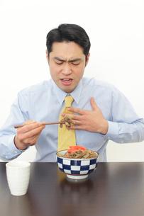 食事中に胸焼けを感じる男性の写真素材 [FYI02028209]
