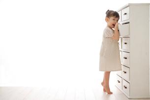 引き出しから捜し物をする女の子の写真素材 [FYI02028252]