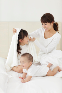 白いベッドの上のお母さんと赤ちゃんと女の子の写真素材 [FYI02028278]
