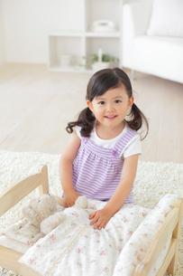 ぬいぐるみをおもちゃのベッドに寝かせて遊ぶ女の子の写真素材 [FYI02028288]