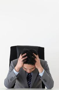 オフィスで頭を抱えるビジネスマンの写真素材 [FYI02028964]
