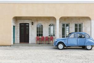 赤い椅子が並ぶオープンカフェとヨーロッパ車の写真素材 [FYI02028969]