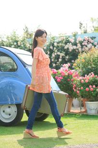 水色の可愛い車とスーツケースと若い女性の写真素材 [FYI02028971]
