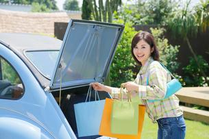 水色の可愛い車から買い物袋を出す若い女性の写真素材 [FYI02028972]