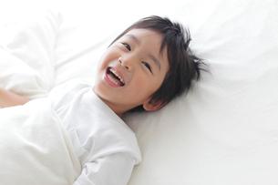 ベッドでくつろぐ寝起きの男の子の写真素材 [FYI02028973]