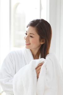 入浴後に窓辺で髪を乾かす女性の写真素材 [FYI02028990]