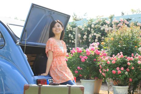 水色の可愛い車とスーツケースと若い女性の写真素材 [FYI02029012]