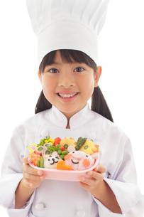 お弁当を見せる女の子のシェフの写真素材 [FYI02029018]