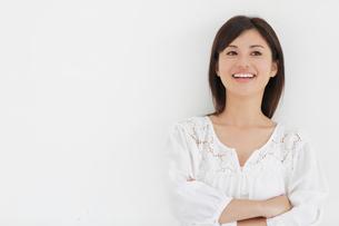 白い壁の前で微笑みながら考える女性の写真素材 [FYI02029036]