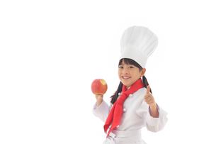 りんごを持つシェフの女の子の写真素材 [FYI02029043]