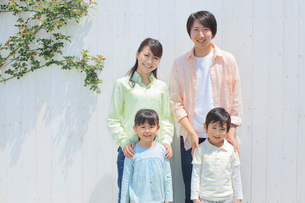 白い板壁の前に並ぶ4人家族の写真素材 [FYI02029047]