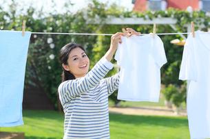 広い庭で洗濯物を干す女性の写真素材 [FYI02029060]