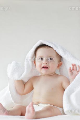 お座りをして頭にタオルをかけている外国人の赤ちゃんの写真素材 [FYI02029069]