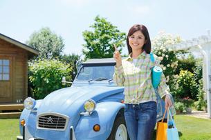 水色の可愛い車の前で指さしポーズをする若い女性の写真素材 [FYI02029086]