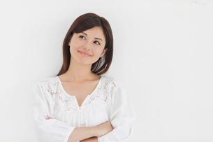 白い壁の前で微笑みながら考える女性の写真素材 [FYI02029102]