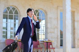 電話をしながらカフェの前を歩く出張中のビジネスマンの写真素材 [FYI02029135]