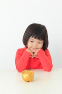 貯金箱を前に悩むおかっぱの女の子の写真素材 [FYI02029138]