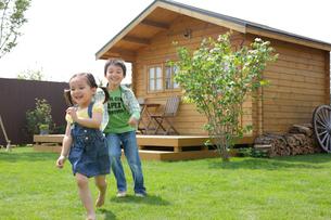 ログハウスの庭で遊ぶ男の子と女の子の写真素材 [FYI02029256]