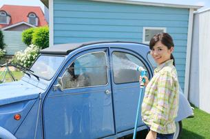 水色の可愛い自動車を洗車する女性の写真素材 [FYI02029264]