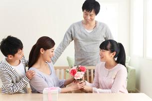母の日のプレゼントを贈る子どもたちと見守るお父さんの写真素材 [FYI02029273]