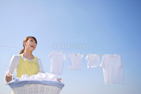 青空の下で家族の洗濯物を干す女性の写真素材 [FYI02029301]