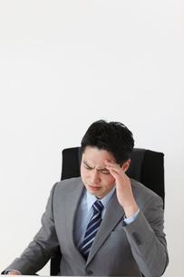 オフィスで頭を抱えるビジネスマンの写真素材 [FYI02029328]