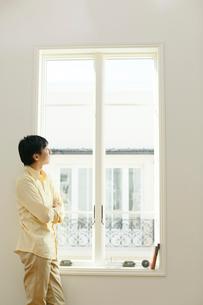 リビングの大きな窓から外を眺める男性の写真素材 [FYI02029340]