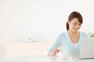 お茶を飲みながらパソコンをする若い女性の写真素材 [FYI02029363]