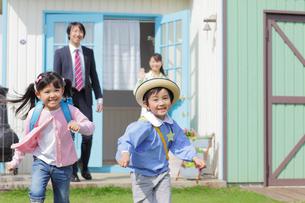 出勤するパパと登校する子供たちを見送るママの写真素材 [FYI02029384]