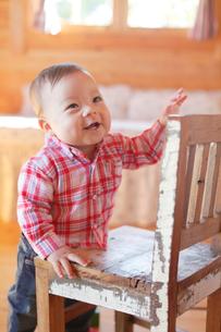 椅子につかまり立ちする赤ちゃんの写真素材 [FYI02029391]