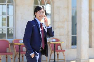 電話をしながらカフェの前を歩くビジネスマンの写真素材 [FYI02029403]
