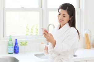 スマートフォンを持つバスローブ姿の女性の写真素材 [FYI02029409]