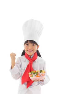 お弁当を見せる女の子のシェフの写真素材 [FYI02029425]