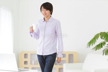 ホームオフィスで仕事中に休憩をする男性の写真素材 [FYI02029444]