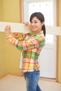 木材を運ぶ女性の写真素材 [FYI02029456]