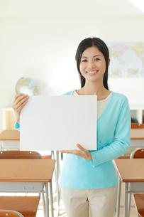 先生と机が沢山並んだ教室の写真素材 [FYI02029458]