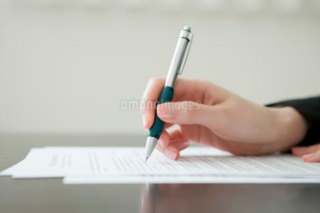 書類に記入をする女性の手の写真素材 [FYI02029460]