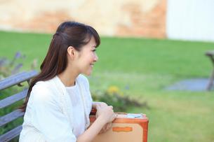 トランクを持ちベンチに座る若い女性の写真素材 [FYI02029476]